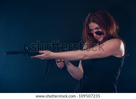 Beautiful woman looks over her sun glasses as she prepares to fire her assault rifle.