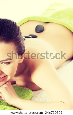Beautiful woman lying and relaxing during stone masasge. Spa concept.  - stock photo