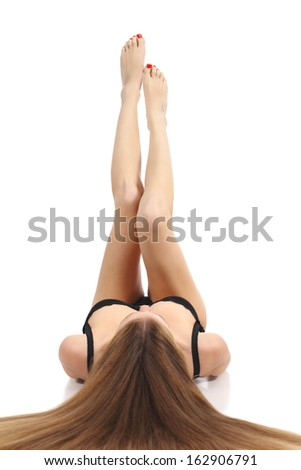 Beautiful woman lying and showing her waxing legs pointing up isolated on a white background              - stock photo