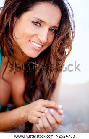 Beautiful woman lying at the beach and smiling - stock photo