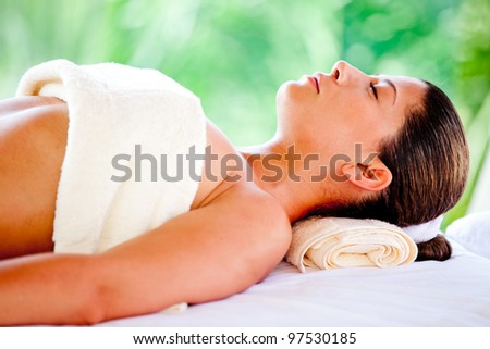 Beautiful woman lying down and relaxing at a spa - stock photo