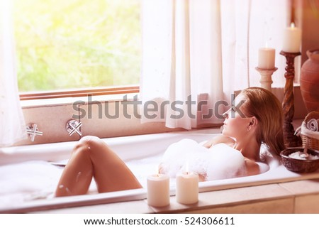 Beautiful woman lying down in the bath with foam and looking at the window, relaxation at home, hygiene and health care, happy and peaceful day spa