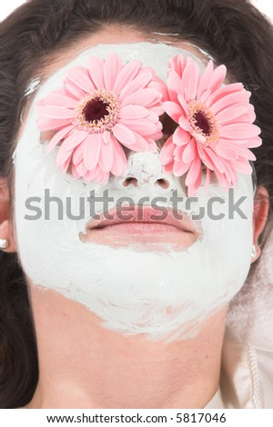 Beautiful woman lying down with a facial mask and flowers on her eyes - stock photo