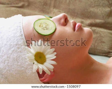 Beautiful woman lying down with cucumber slices and daisy. - stock photo
