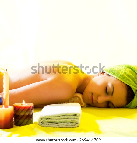 Beautiful woman lying down with towel on her head getting ready for the spa treatment    - stock photo