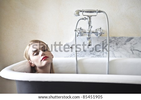 Beautiful woman lying in a bathtub - stock photo