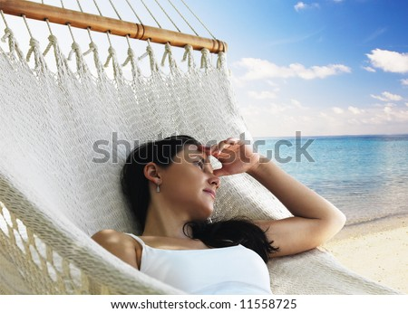 Beautiful woman lying in hammock near the ocean - stock photo