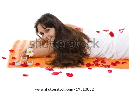 Beautiful Woman lying in the towel with petals . - stock photo