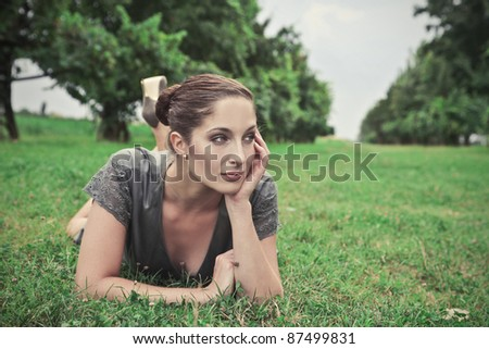Beautiful woman lying on a green meadow - stock photo