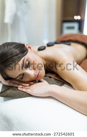 Beautiful woman lying on a massage table and relaxing while being massaged - stock photo