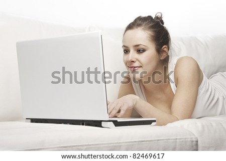 Beautiful woman lying on a sofa and using a laptop - stock photo