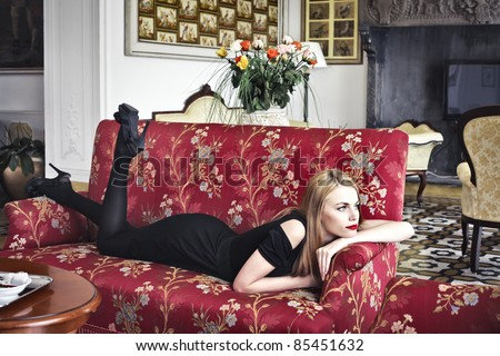 Beautiful woman lying on a sofa in a luxury hotel - stock photo