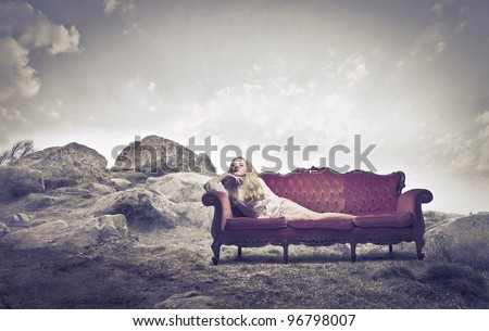 Beautiful woman lying on a sofa on a hill - stock photo