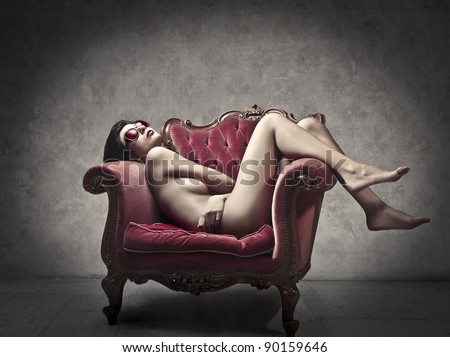 Beautiful woman lying on an armchair - stock photo
