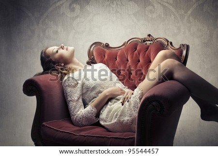 Beautiful woman lying on an armchair with a sensual pose