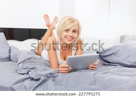 beautiful woman lying on bed using digital tablet, young blond girl white underwear in modern bedroom - stock photo