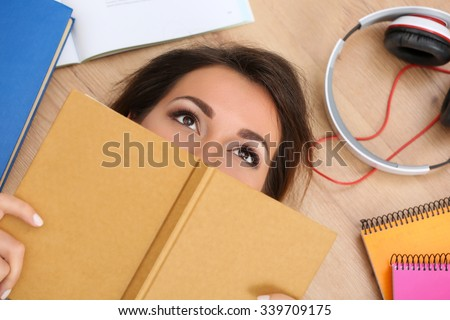 Beautiful woman lying on floor covering face with book dreaming. Female student studying using textbooks. Education, learning, self development, leisure, pastime, library or bookshop concept - stock photo