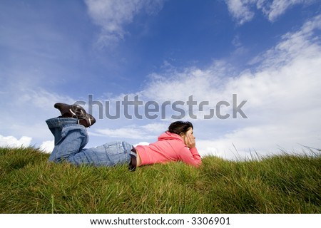 Beautiful woman lying on grass with blue sky - stock photo