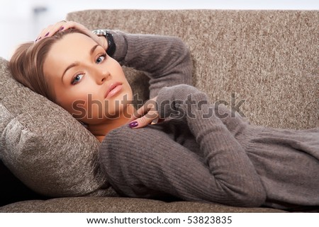 Beautiful woman lying on the couch - stock photo