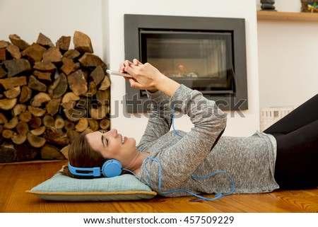 Beautiful woman lying on the floor and listen music  - stock photo