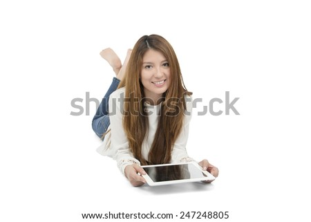 Beautiful woman lying on the floor while holding her digital tablet against a white background