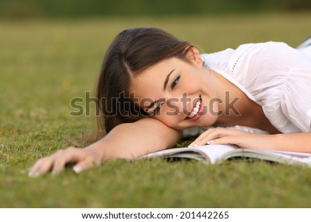 Beautiful woman lying on the grass reading a paper book with a green unfocused background               - stock photo