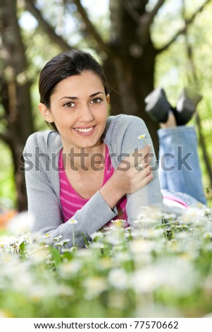 beautiful woman lying on the grass with flowers (focus on girl) - stock photo