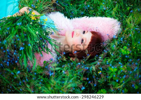 Beautiful woman lying on the green grass among the wild flowers - stock photo