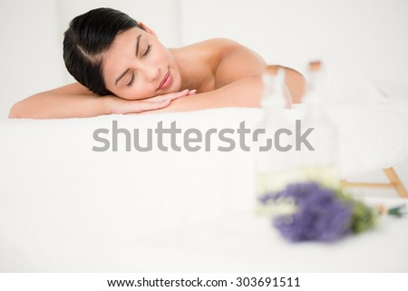 Beautiful woman lying on the massage table at the health spa - stock photo