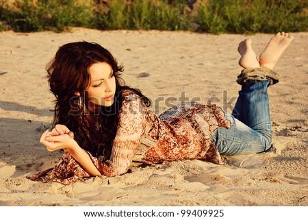 Beautiful woman lying on the sand - stock photo