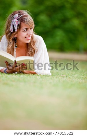 Beautiful woman lying outdoors reading a book