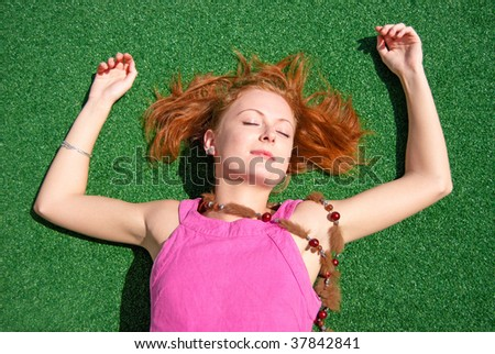 Beautiful woman lying over artificial green grass