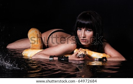 Beautiful woman lying with Python in water - stock photo