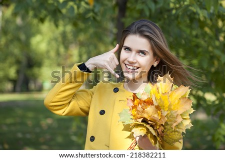 Beautiful woman making a call me gesture in autumn park - stock photo