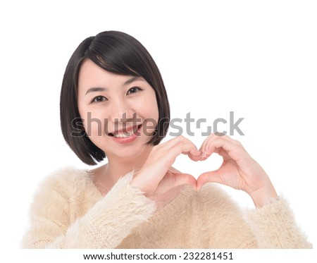 Beautiful woman making a heart shape with her hands - stock photo