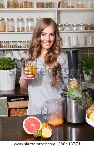 Beautiful woman making detox juice with juicer - stock photo