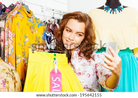 Beautiful woman making photo with mobile in shop - stock photo