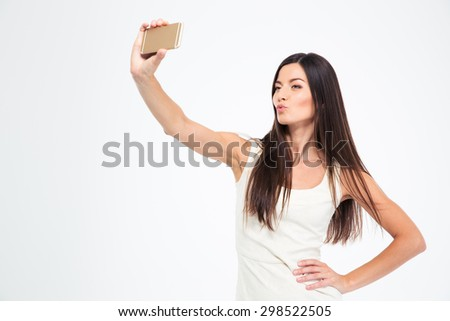 Beautiful woman making selfie photo on smartphone isolated on a white backgorund - stock photo