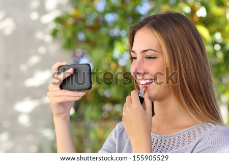 Beautiful woman making up using a smart phone as a mirror with a green background