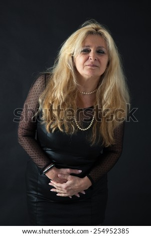 Beautiful woman man doing different expressions in different sets of clothes: stomachache - stock photo