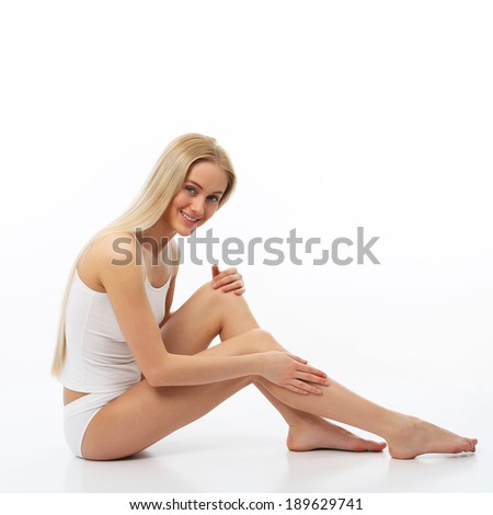 Beautiful woman massaging his legs with cream - stock photo