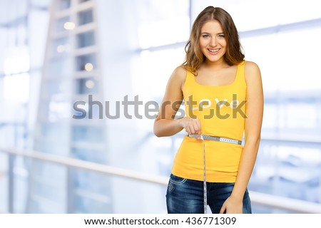 Beautiful woman measuring her waist with a measuring tape - stock photo