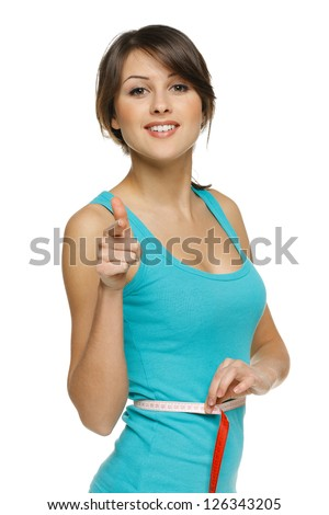 Beautiful woman measuring her waist with a measuring tape pointing at you, over white background