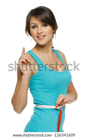 Beautiful woman measuring her waist with a measuring tape with finger up, over white background