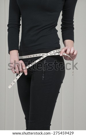 Beautiful woman measuring her waist with a tailors tape - stock photo