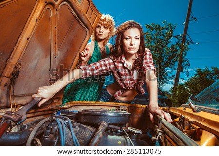 Beautiful woman mechanic is repairing a car another woman is watching. - stock photo