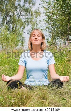 Beautiful woman meditates on the nature - stock photo