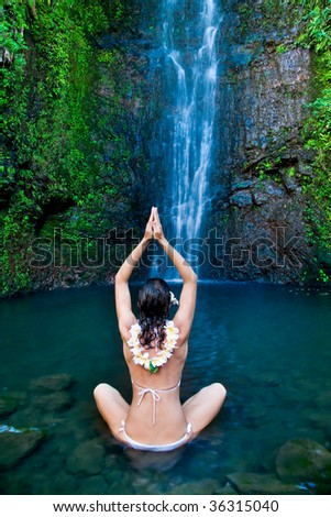 beautiful woman meditating in front of tropical waterfall
