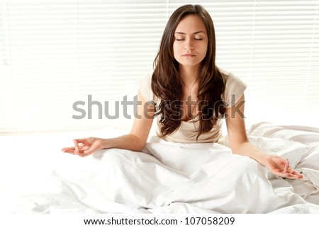 Beautiful woman meditating on a bed on a light background - stock photo