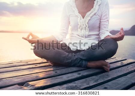 beautiful woman meditating on a boardwalk at sunset - stock photo